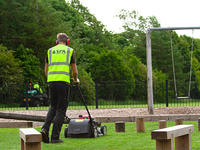 landscape contractors using pedestrian Honda mower in play area