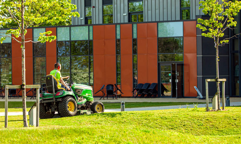 john deere mower cutting grass on uneven terrain