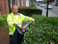 contractor in hi-vis litter picking around shrubbery